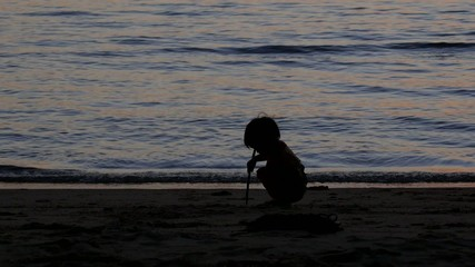 Adorable Kid Playing with Sand on the Beach on Sunset Time.
