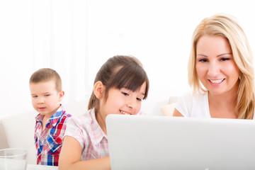 Mutter mit Kindern vorm Laptop
