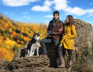 Young couple walking their husky dog in autumn countryside