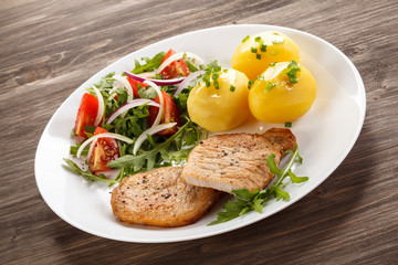 Fried steaks, boiled potatoes and vegetable salad