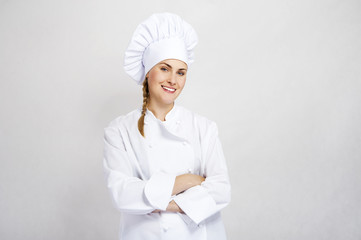 A young, female chef in a traditional hat and coat.