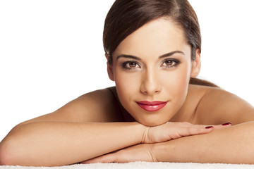 Portrait of beautiful young woman lying down on towel