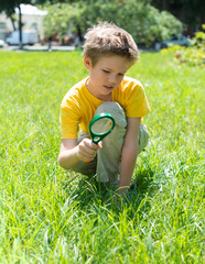 Kid with magnifying glass outdoors.