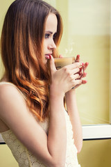 girl at the window with a hot coffee early in the morning