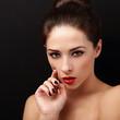 Flirting sexy makeup female model with hand near face. Closeup