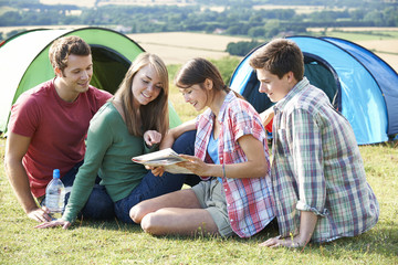 Group Of Young Friends Camping In Countryside Reading Map