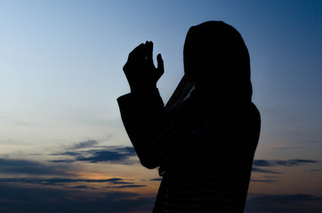 Silhouettes of a women praying during sunset