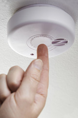 Close Up Of Hand Testing Domestic Smoke Alarm