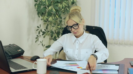 Beautiful secretary studying charts and reports related to the