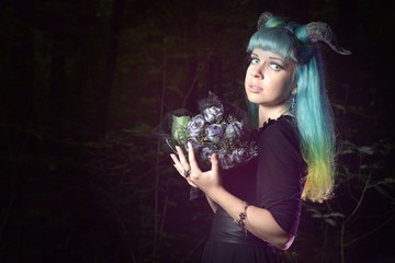 Beautiful woman with color hair and horns holds black bouquet