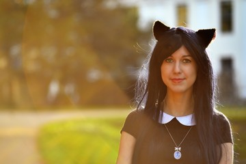 Cute girl with toy cat ears on head in sunbeam light