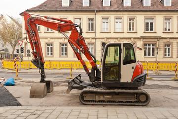 Strassenbau - Ein Kompaktbagger steht am Strassenrand