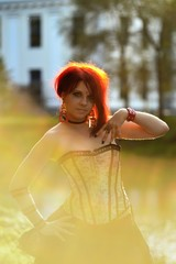 Beautiful redhair woman on natural background in Victorian suit