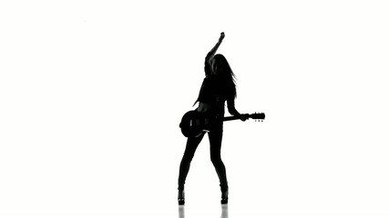Silhouette of a young girl dancing with electric guitar on a