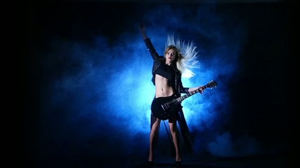 Headbanging sexy woman plays guitar at the concert. Slow motion.