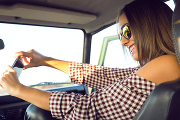 Fashion beautiful girl taking selfie with smartphone in the car.