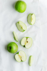 Green apples over white cloth