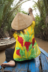 Vietnamese woman rows a boat in Mekong River in Vietnam