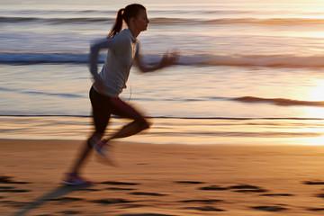 fitness woman running on beach