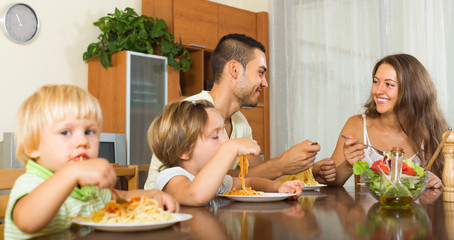 Family of four eating spaghetti
