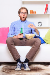Surprised man in front of TV wirh popcorn and beer