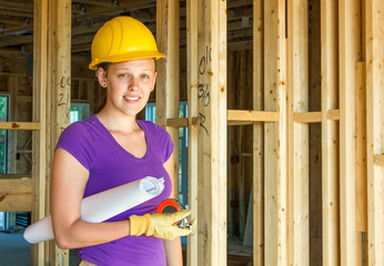 Woman in hardhat with architectural drawings