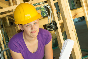Woman in hardhat looking frustrated