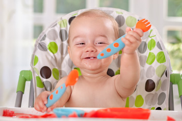 Happy smiling cute baby holding spoon and fork