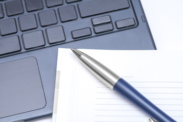 Notepad and pen on keyboard
