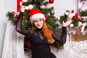 Cheerful red-haired girl in the Santa Claus hat