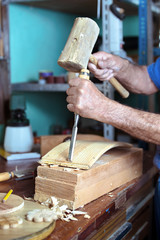 hands of cabinetmaker carving wood with a chisel and hammer