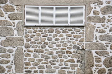 white window on a wall made of stones