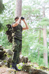 soldier with binocular and backpack in forest