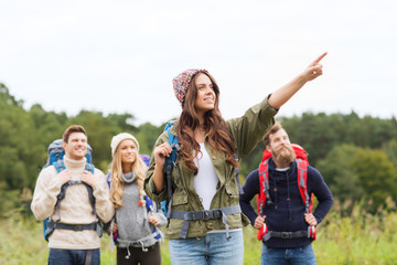smiling hikers with backpacks pointing finger