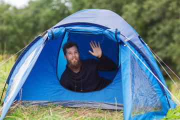 smiling male tourist with beard in tent