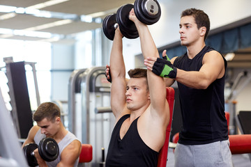 group of men with dumbbells in gym