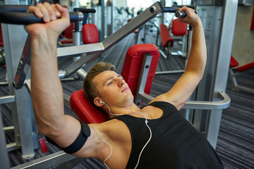 young man with earphones exercising on gym machine