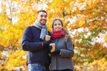 smiling couple with coffee cups in autumn park