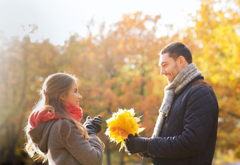 smiling couple with bunch of leaves in autumn park