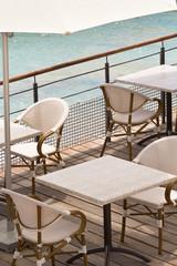 tables sur terrasse au bord de l'eau