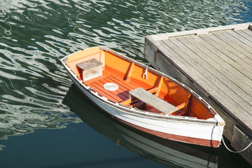 Quaint dinghy, white and orange, tied to floating pier