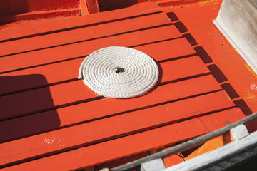White roped coiled on orange slatted floor of dinghy.