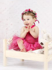 Stunning little girl sitting on the bed with floral wreath