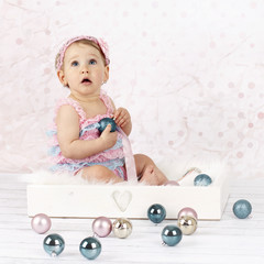 Little baby girl playing with christmas balls