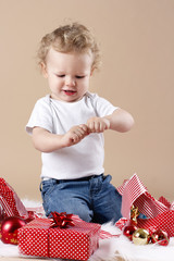Little boy unwrapping christmas presents
