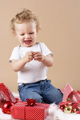 Happy little toddler unwrapping christmas presents