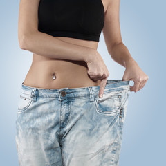 Woman shows her weight loss by wearing an old jeans.