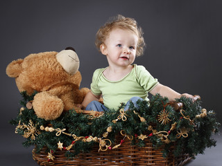 Little boy sitting in the christmas basket with teddy bear