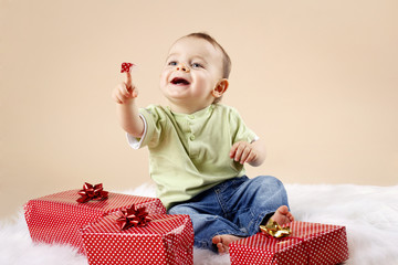 Cute little baby boy unwrapping christmas presents
