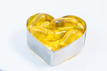 Fish Oil pills on heart   isolated